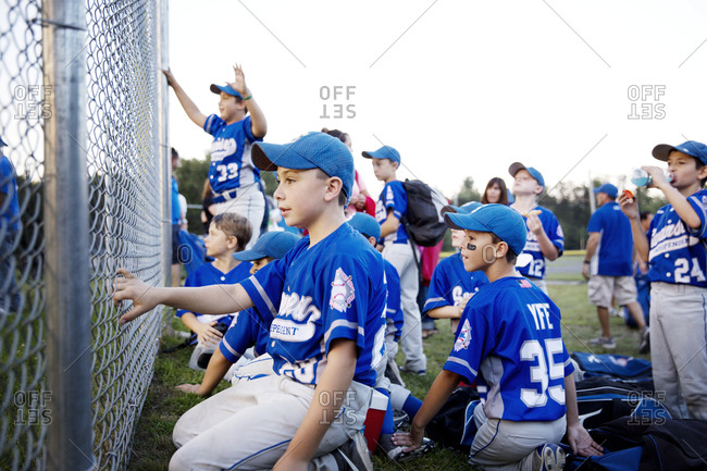 A youth league team watches the field from behind a fence