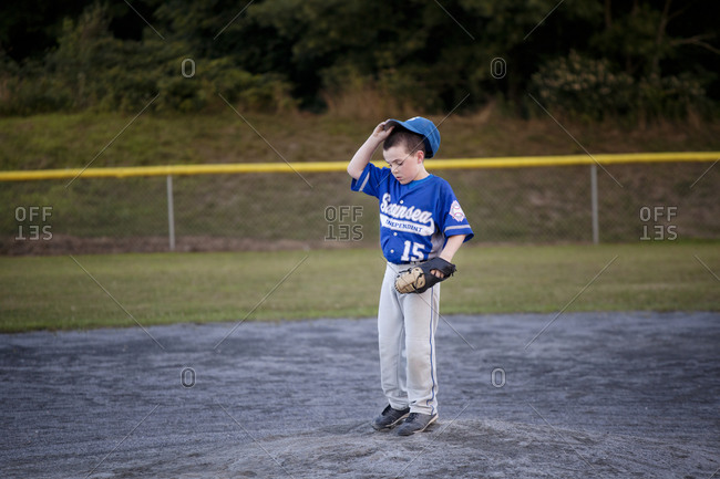 A youth league player adjusts his baseball cap