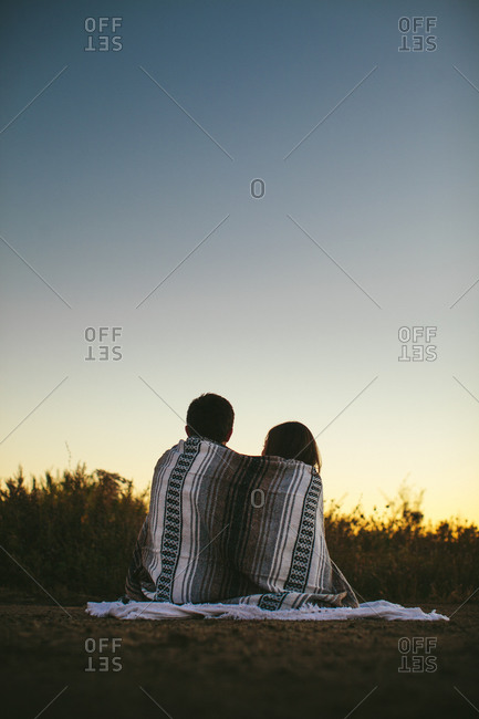 Couple watching the sunset in a field
