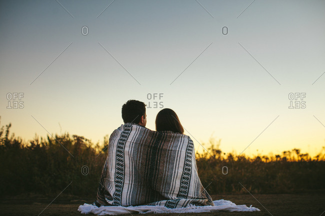 Couple sitting in a field at sunset
