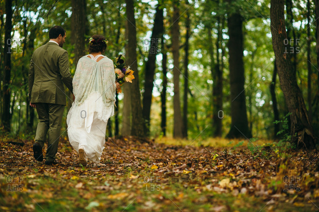 Bride and groom walking in a forest