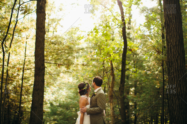 Bride and groom standing in a forest