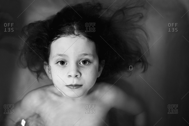 A little girl floats in a bathtub