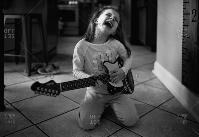 A little girl rocks out on a fake guitar