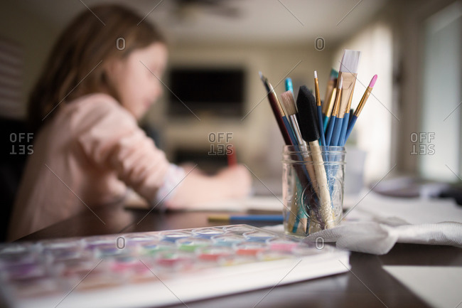 A little girl paints with watercolors