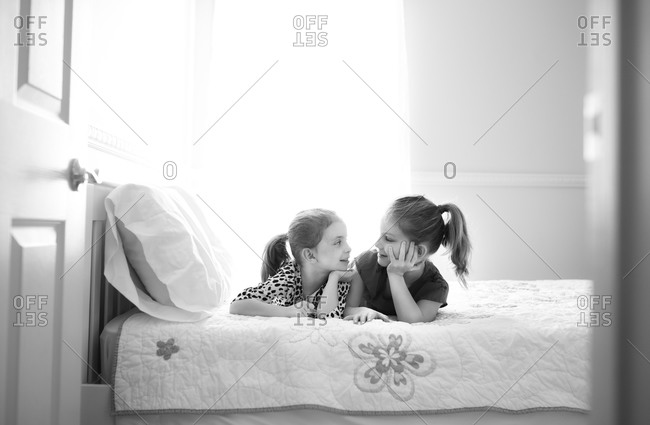Two little girls lie on a bed together