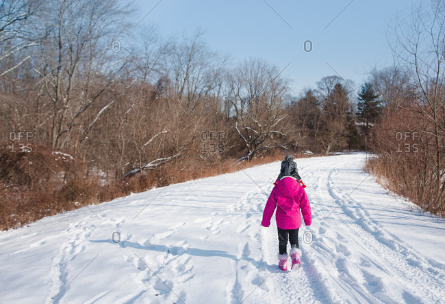 A little girl treks down a snowy road