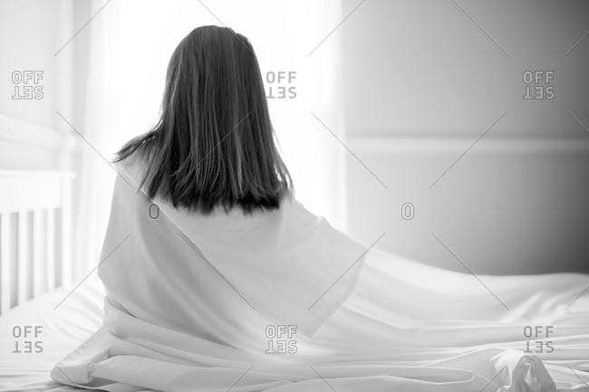 A little girl wrapped in a white sheet