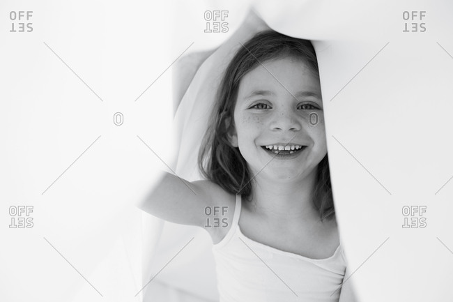 A little girl plays underneath bed sheets