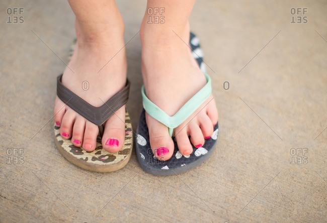A little girl wearing mismatched flip flops