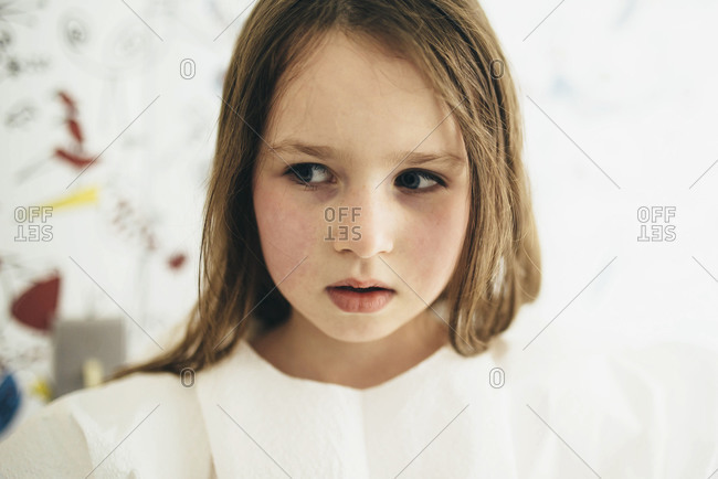A little girl looks cautiously to the side
