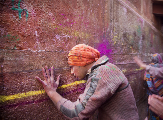 March 5, 2015: A man leans against  wall, taking a break from Holi, the Hindu festival of color in Mathrua, India