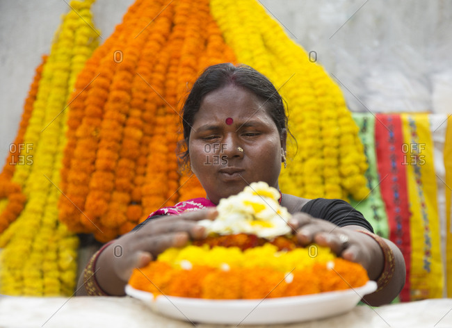 February 27, 2015: A woman prepares Buddhist offerings for to sell at Bodh Gaya in India