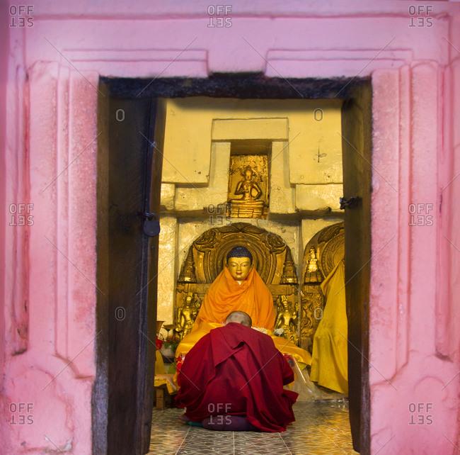 A monk prays at the feet of a statue of Buddha at Bodh Gaya, India