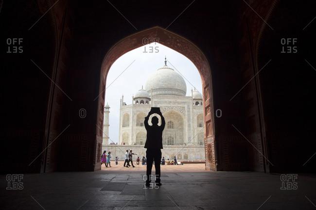 A man takes a photo of the Taj Mahal in Agra, India