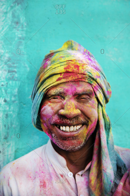 March 5, 2015: A man smiling while covered in powder during Holi, the Hindu festival of color in Mathura, India