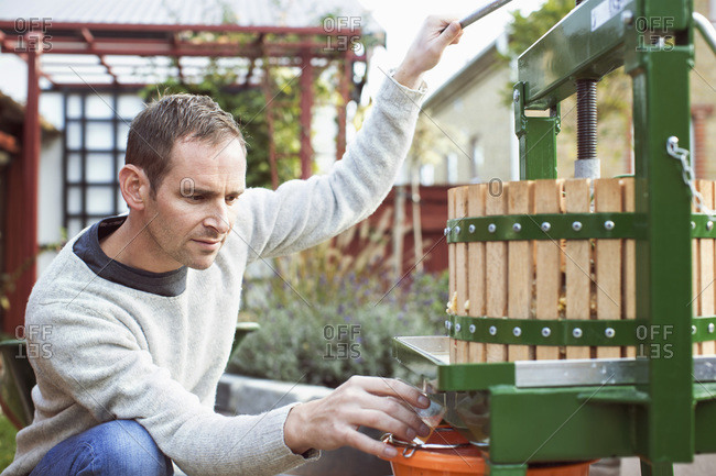 Man collecting fresh apple juice from cider in glass