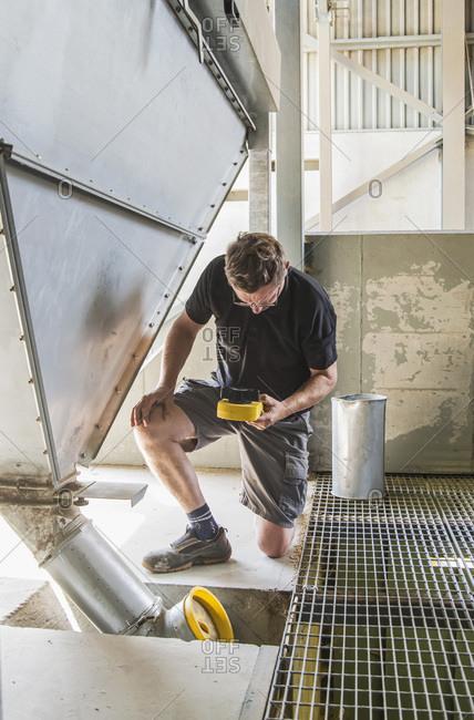 Farmer measuring crop moisture content at factory