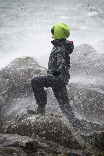 Side view of boy with arms outstretched enjoying snow storm on a rock