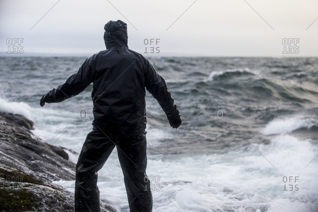 Rear view of man in raincoat standing on rock by sea