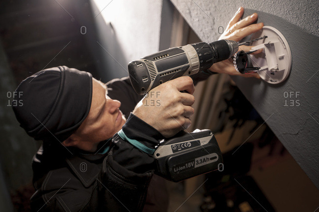 High angle view of man fitting a security camera on wall