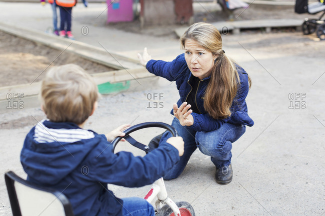 Angry teacher shouting at boy on a tricycle