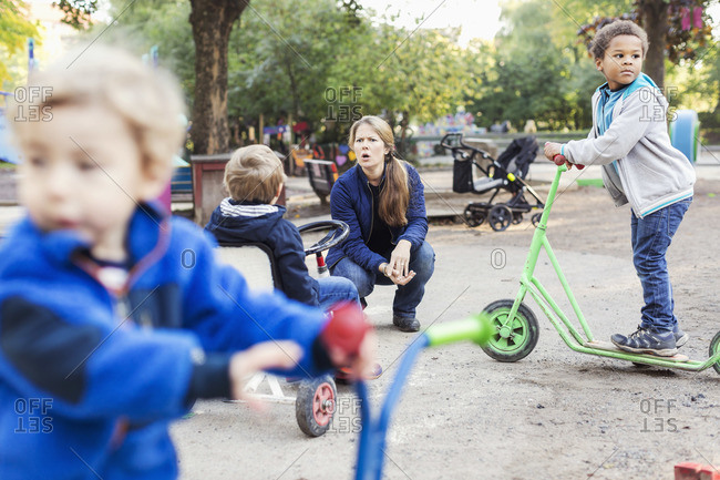Angry teacher with children playing at the playground
