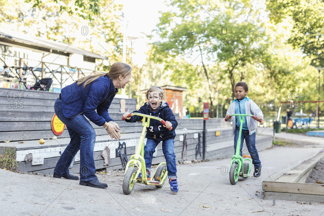 Teacher motivating children to push scooters during race