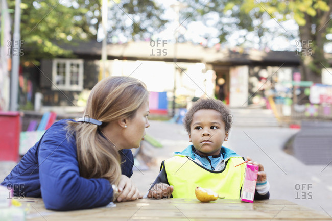Teacher looking at student holding juice box outside kindergarten