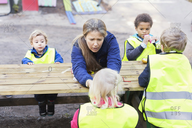 Children in protective jackets sitting with teacher at table