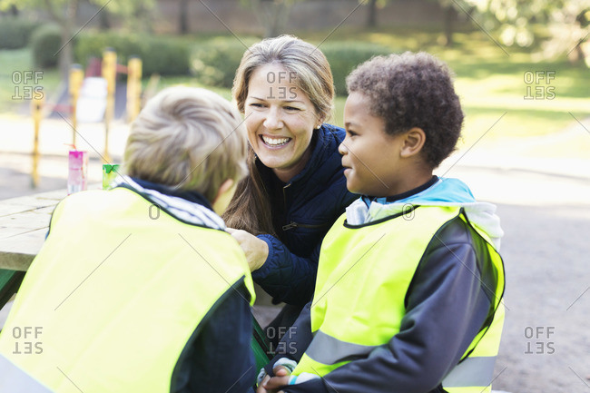Happy teacher with children in reflective jackets