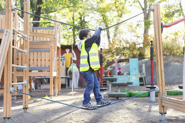 Side view of boy balancing on rope at playground