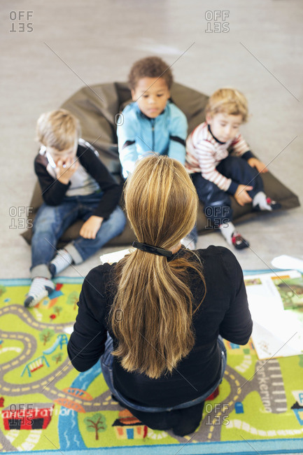 High angle view of teacher sitting in front of children at kindergarten