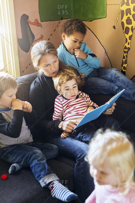 Teacher reading a story to children in kindergarten