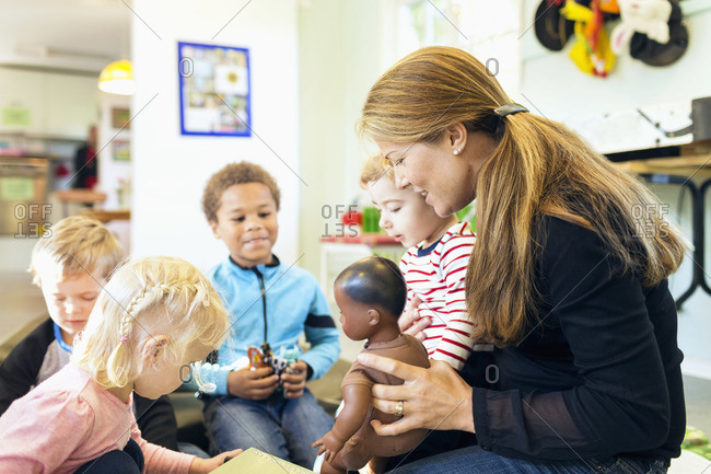 Teacher and children with toys in kindergarten