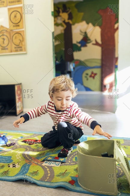 Boy removing toys from box in kindergarten