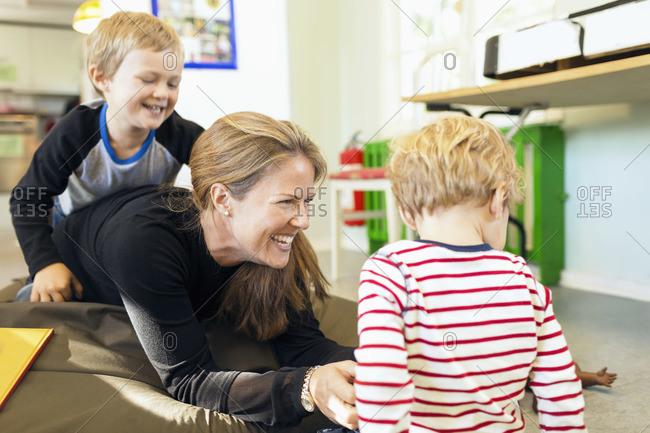 Happy teacher playing with children in kindergarten