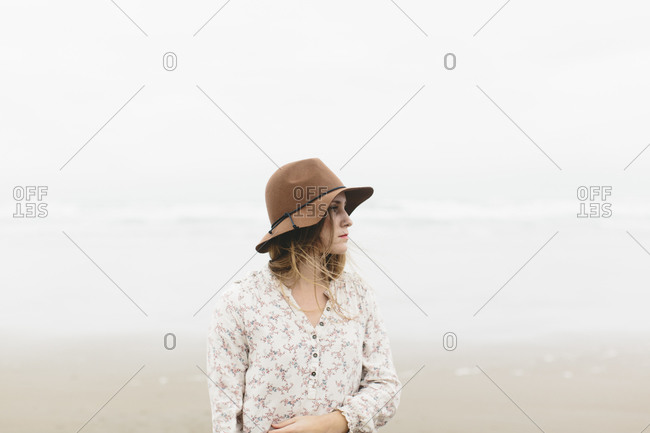 Young woman standing on gray beach