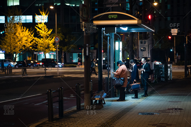 Osaka, Japan - November 12, 2014: Commuters at a bus stop in the Tosabori district