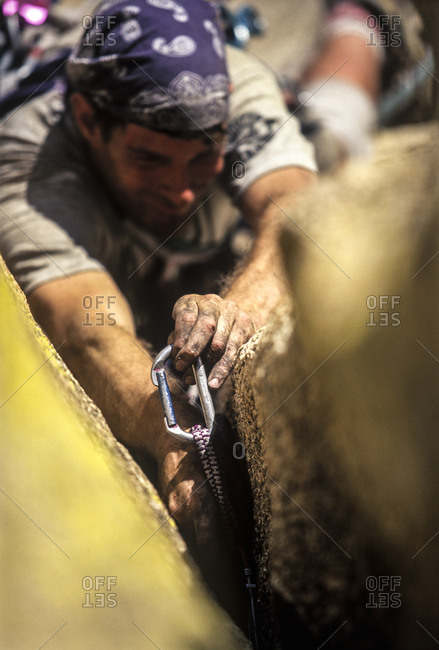 A climber hooks a carabiner to the rock wall