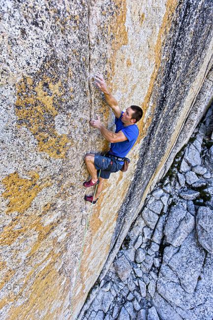 A rock climber heads up a vertical rock wall