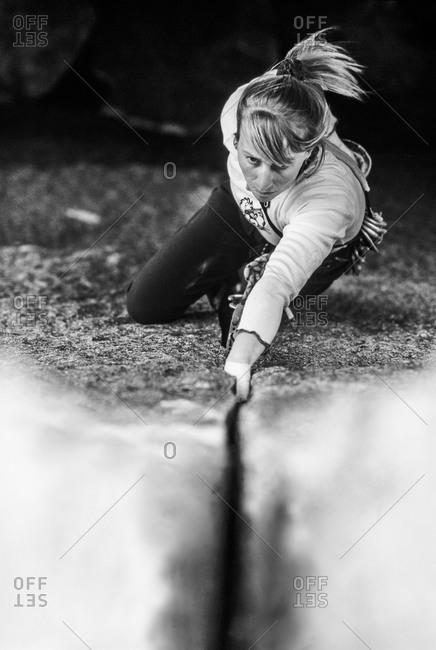 A woman climbs up a vertical rock wall