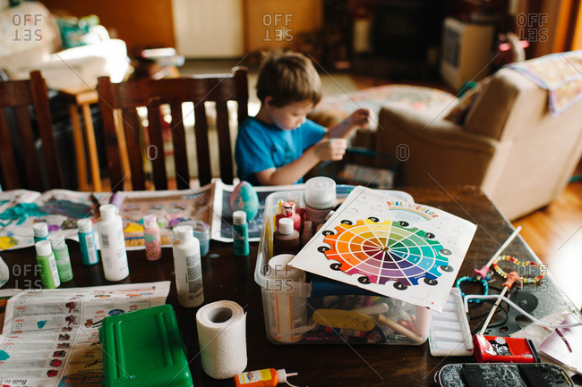 Young boy painting Easter eggs at home