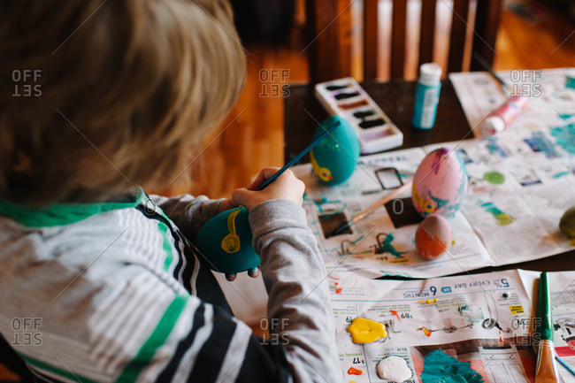 Young boy painting Easter eggs at a table