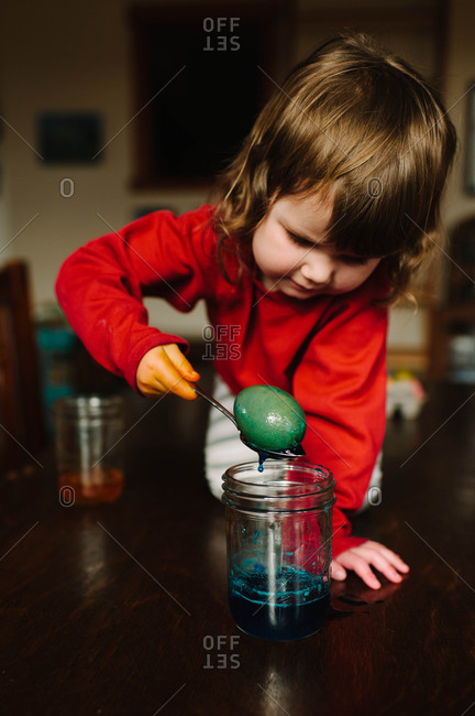 Young girl dyeing Easter eggs in a jar