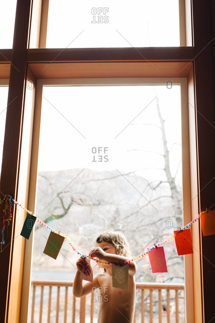Young girl pinning Eater cards by the window