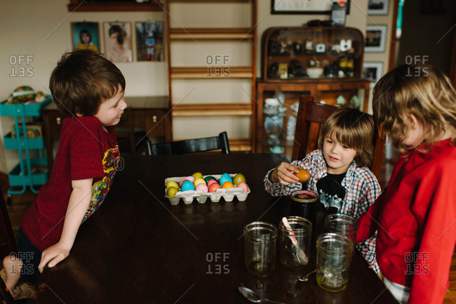 Children dyeing Easter eggs together at a table