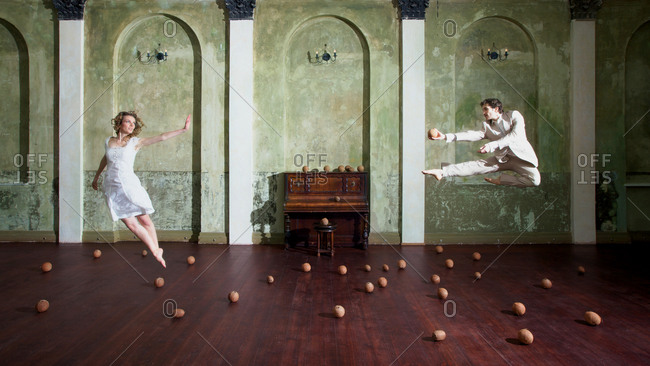 Dancers leaping in a room filled with coconuts