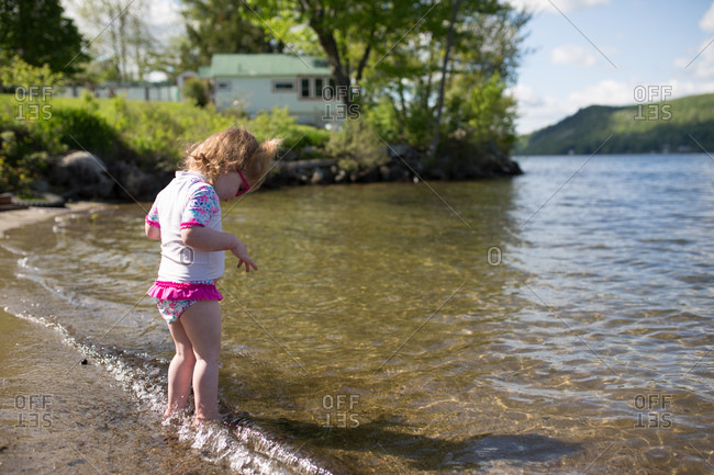 Girl cautiously stepping into lake