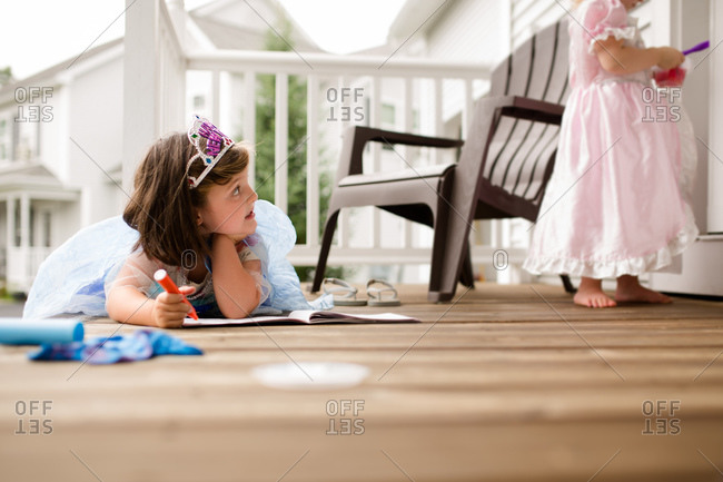 Two girls in princess dresses drawing on porch